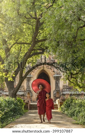 Little Myanmar monk walking outside monastery, Bagan, Myanmar - stock photo