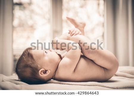 Little naked baby girl lying on her back and holding his feet - stock photo