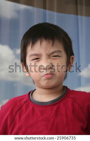 Little naughty boy in red tee pouting - stock photo
