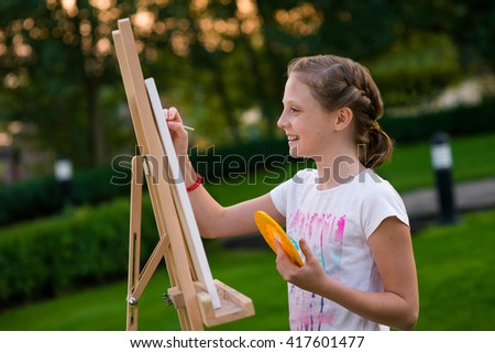 Little new artist is busy with painting at her leisure time. Talented girl copies the surrounging landscape for paper on her easel. - stock photo