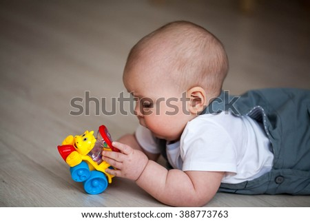 Little newborn baby lying on the floor and playing with toy car - stock photo