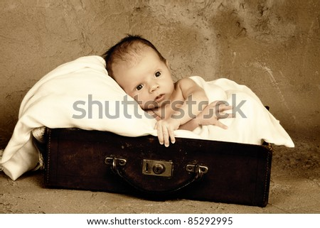 Little newborn baby of 18 days old in an old vintage leather suitcase - stock photo