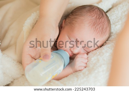 little newborn baby sleeps and eats a mixture of milk bottles - stock photo