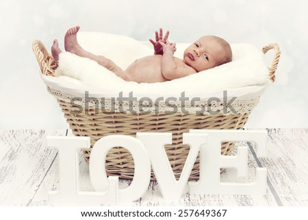 Little newborn lying in the wicker basket and looking to the camera - stock photo
