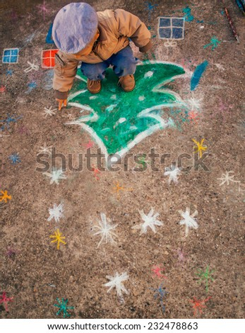 Little painter drawing Christmas tree and gifts on the street. - stock photo