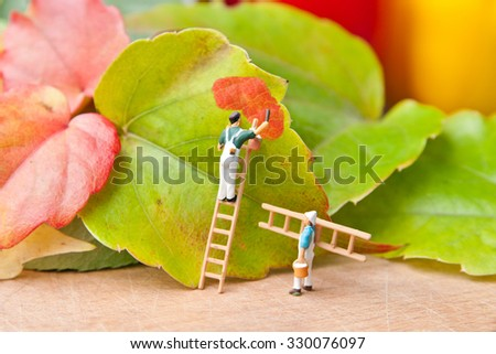 Little people paint leaf on autumn colors. The concept of teamwork. - stock photo