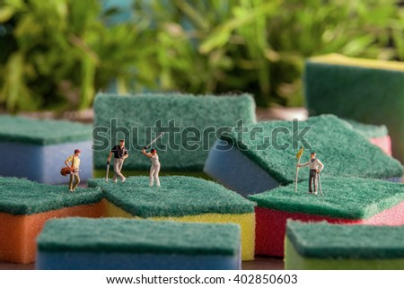 Little people play golf on the sponge to wash. The concept of sport. - stock photo