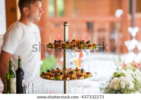 Little pieces of fruits and cheese stand behind the bottle of wine - stock photo