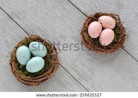Little pink and blue speckled easter eggs in mossy vine nests on rustic wooden background - stock photo