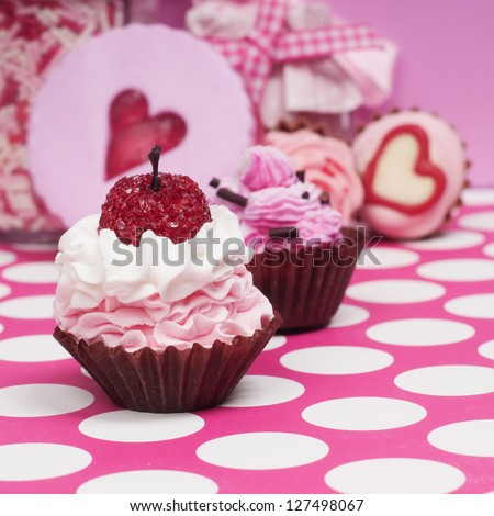 Little pink baby cupcakes with jam cookie and bonbons in the background. - stock photo