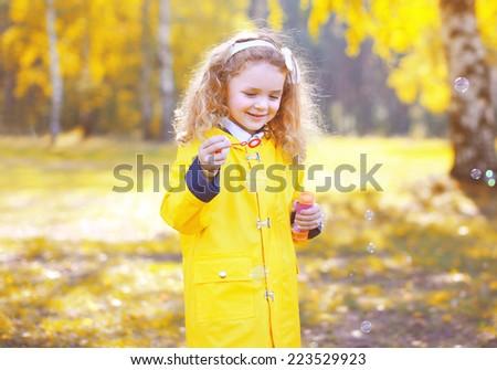 Little positive child having fun outdoors in autumn park - stock photo