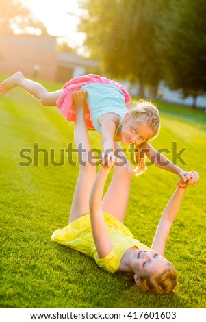 Little prankers rest in the park and make some noise while playing with each other. Holding the younger sister with hands and legs in the air. - stock photo