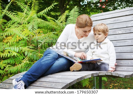 Little preschool boy and his mother sitting on bench in park and reading fairytale book together. - stock photo