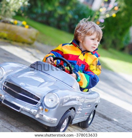 Little preschool boy driving big toy old vintage car and having fun, outdoors. Active leisure with kids outdoors  on warm spring or autumn day. - stock photo
