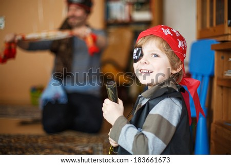 Little preschool boy of 4 years celebrating birthday in pirate costume, indoors with father on background - stock photo