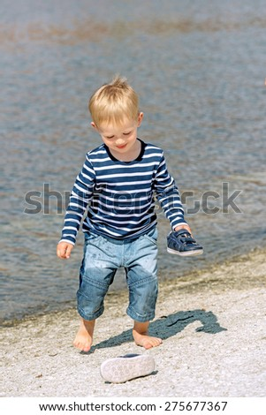 Little preschool boy playing on shore outdoors - stock photo