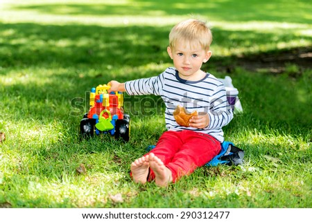 Little preschool boy playing with big toy car and having fun, outdoors. - stock photo
