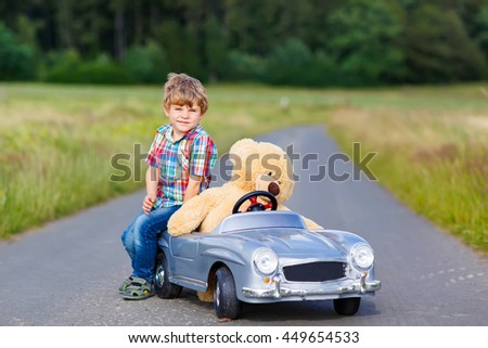 Little preschool kid boy driving big toy car and having fun with his plush toy bear, outdoors. Child enjoying warm summer day in nature landscape - stock photo