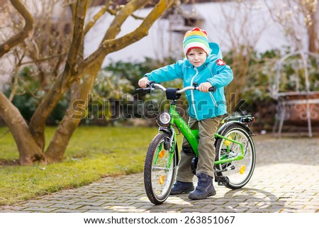 Little preschool kid boy riding with his first green bike in the city. Happy child in colorful clothes. Active leisure for kids outdoors. - stock photo