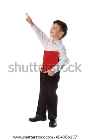 Little preschooler in casual clothing with book pointing up to empty space, isolated on white - stock photo
