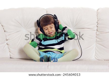 Little pretty boy listening to music - stock photo