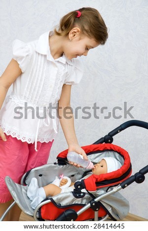 Little pretty caucasian girl playing with doll - stock photo