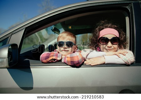 little pretty girl and cute boy driving fathers car - stock photo