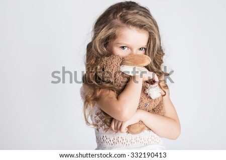 Little pretty girl hugging her toy rabbit and hiding her face with embarrassment or shame or modesty - stock photo