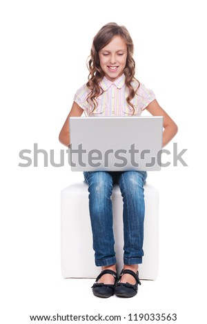 little pretty girl looking at laptop and smiling. isolated on white background - stock photo
