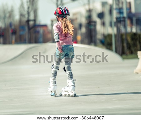 Little pretty girl on roller skates in helmet at a park. back view - stock photo