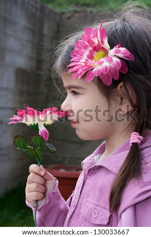 Little, pretty girl smelling beautiful pink flower - stock photo