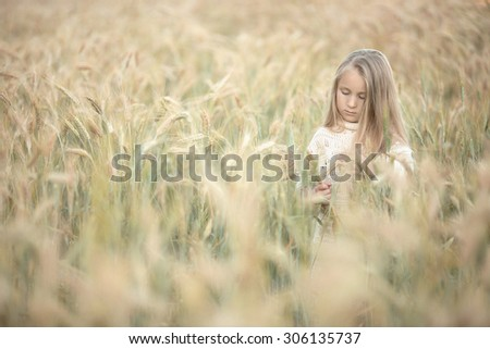 little pretty girl with long blond hair standing in the field of wheat of corn and thinking at summer time - stock photo