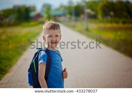 Little pretty schoolboy standing on the street with his backpack  - stock photo