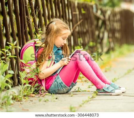 Little pretty schoolgirl reading a book sitting on the street - stock photo