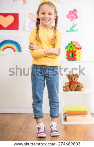 Little pretty smiling girl in full length in yellow  pullover on colorful background. - stock photo