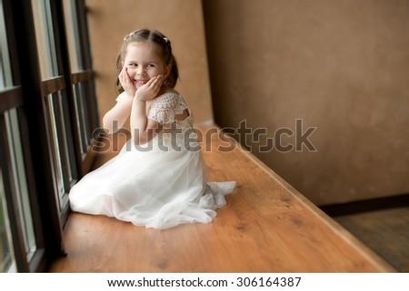 little pretty smiling happy girl in white dress sitting near the window - stock photo