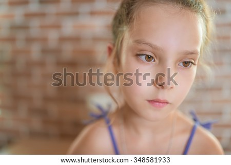 Little pretty thoughtful girl sitting on the brick wall background. - stock photo