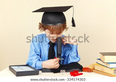Little professor in academic hat looking through a microscope at his desk - stock photo