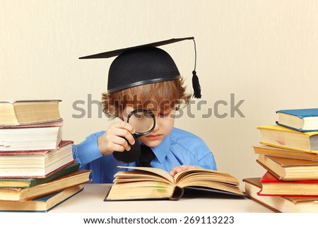 Little professor in academic hat reading an old books with a magnifying glass - stock photo