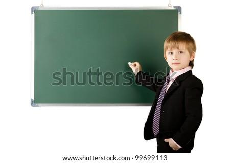 little pupil writes with chalk  on blackboard - stock photo