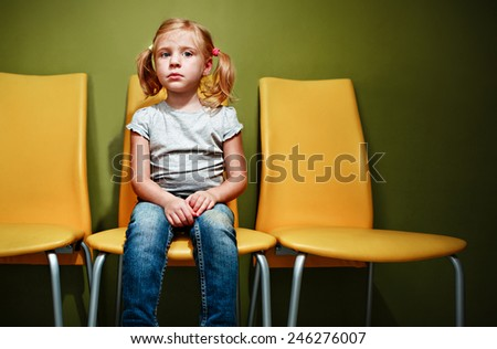 Little redhead girl waiting in reception room. - stock photo