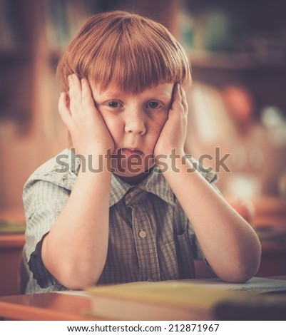 Little redhead schoolboy behind school desk during lesson  - stock photo