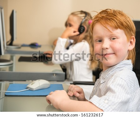 Little redhead schoolboy in front of desktop computer in school  - stock photo