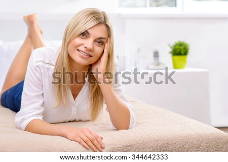 Little rest. Appealing young female tourist is lying in her hotel bed and enjoying the moment. - stock photo