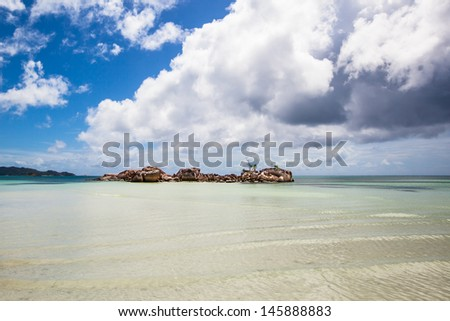 little rocky island in the sea under a blue sky with some white clouds, Seychelles - stock photo