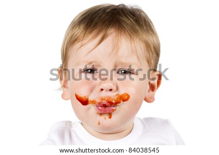 Little sad boy with jam on his face. Isolated on white. - stock photo