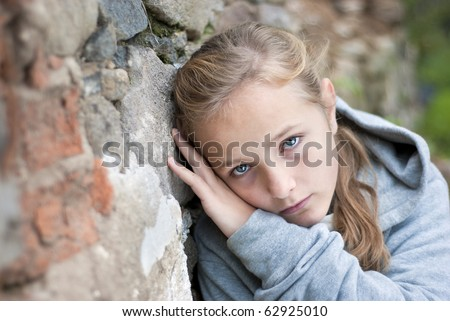 Little sad child in outdoor. - stock photo