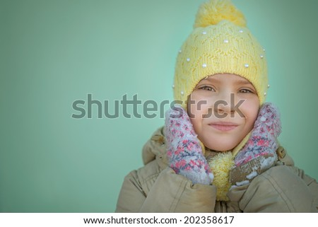 Little sad girl in pink coat and yellow cap - stock photo
