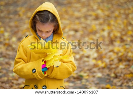 Little sad girl in yellow coat holding autumn leaves. - stock photo