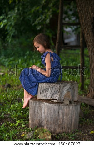 little sad girl is sitting alone outdoors. - stock photo